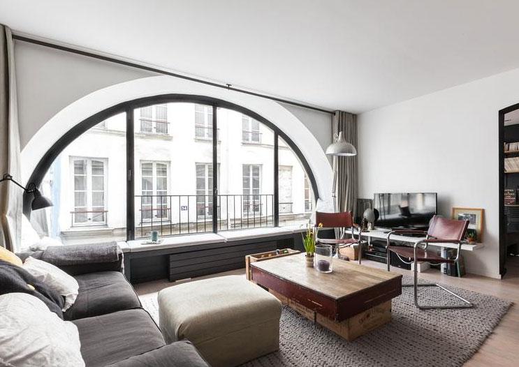 Paris 3e, quartier du Temple : le salon avec sa grande baie vitrée en arc